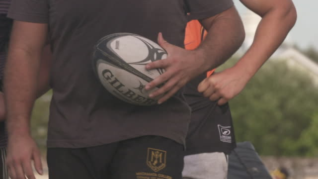 Slow motion footage of rugby players walking with ball and standing in group during refreshment break