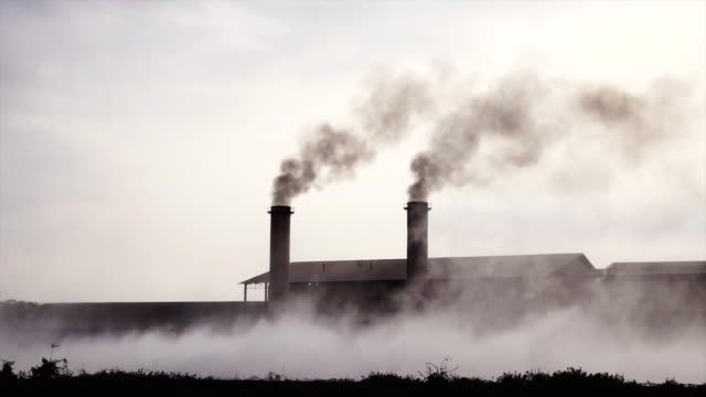 4k slow motion footage of smokestack factory at the countryside at evening time, industry and pollution concept - officina video stock e b–roll
