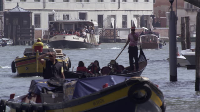 Slow motion footage of tourists traveling on a gondola across a busy canal.