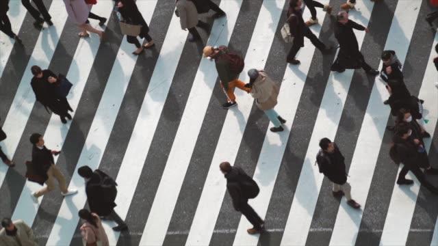 4K Slow Motion-Aufnahmen der Verkehrsstraßenkreuzung in der Hauptverkehrszeit und drängen Fußgänger zu Fuß über die Straße in Shibuya Bezirk Tokio Stadt, Japan. Japanisches Kultur-und Einkaufsbereichskonzept