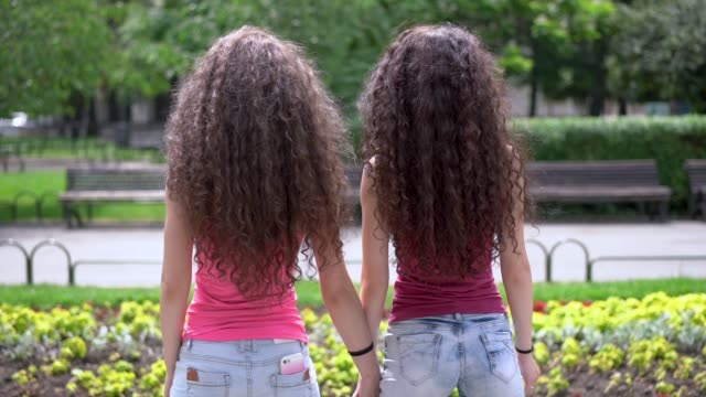 slow motion footage of twin sisters holding hands and tossing hairs - hair toss stock videos & royalty-free footage