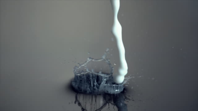 slow motion footage of white liquid falling into water - splash crown stock videos & royalty-free footage