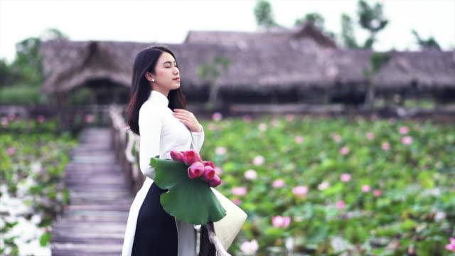 vídeos y material grabado en eventos de stock de 4k cámara lenta imágenes retrato de hermosa mujer vietnamita sosteniendo el loto rosa y obtener aire fresco en el puente de madera en concepto de lotus big lake, vietnam, asia o asia sudoriental viajes - posa del loto