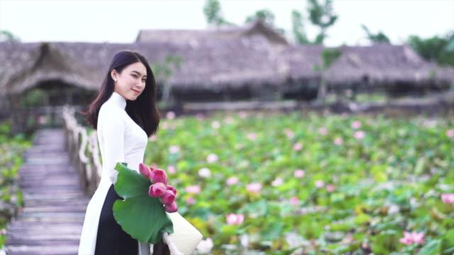 vídeos y material grabado en eventos de stock de 4k cámara lenta imágenes retrato de hermosa mujer vietnamita sosteniendo el loto rosa y sonriendo en el puente de madera en concepto de viajes de lotus grande lago, vietnam, asia o asia sudoriental - posa del loto
