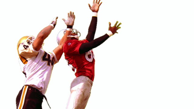 overexposed slow motion football player jumping up to catch ball as opposing player tries to block him - overexposed video stock e b–roll