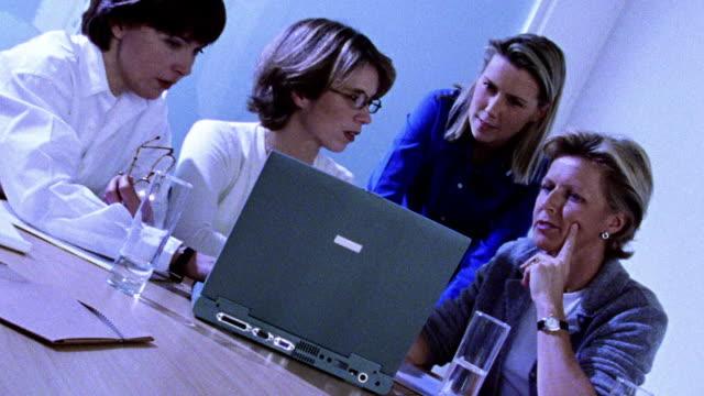 vídeos de stock e filmes b-roll de blue selective focus slow motion four businesswomen working, talking + smiling at laptop computer - super exposto