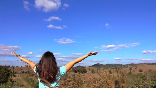Slow motion Freedom of Woman with arm raised on top of mountain