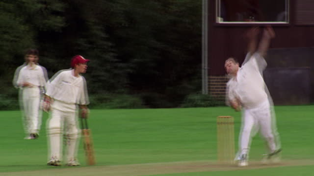 slow motion PAN from bowler pitching ball to batsman in game of cricket / Hertfordshire, England