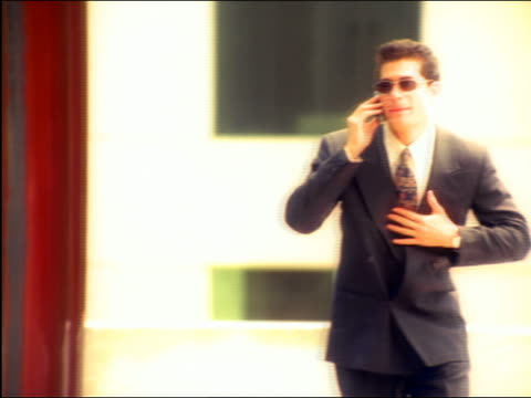 overexposed slow motion pan from businessman talking on cell phone to his reflection running on bldg - overexposed stock videos & royalty-free footage