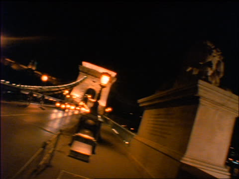 slow motion swish pan from lion statue to traffic on chain bridge at night / budapest, hungary - chain bridge suspension bridge stock-videos und b-roll-filmmaterial