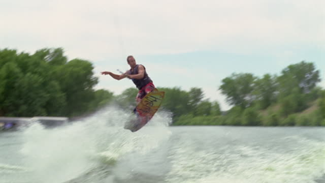 Slow Motion, POV from the back of a boat pulling a man on a waterboard in a lake. The man jumps very high over the wake, from camera right to left.