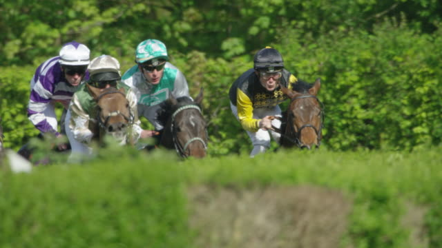 Slow motion Gallop Horse Race, curve entering home straight, jockeys close up