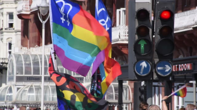Slow motion gay and lesbian flags are waved