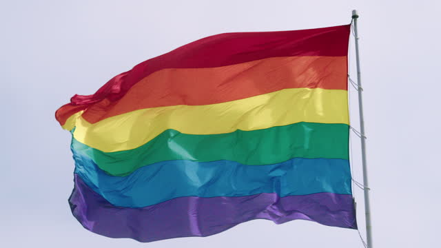 slow motion gay pride flag blowing in the wind. - pole stock videos & royalty-free footage