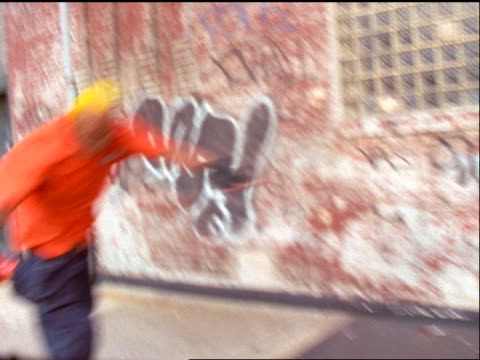 slow motion pan gen x man with yellow hair inline skates on city sidewalk past camera / nyc - 1998 stock-videos und b-roll-filmmaterial