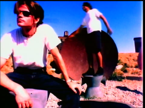 slow motion Generation X man posing on pedestal outdoors / other man with sunglasses sitting in foreground