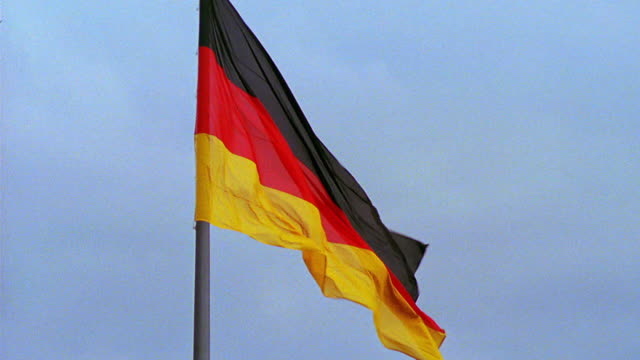 slow motion german flag on pole blowing in wind / berlin - german flag stock videos & royalty-free footage