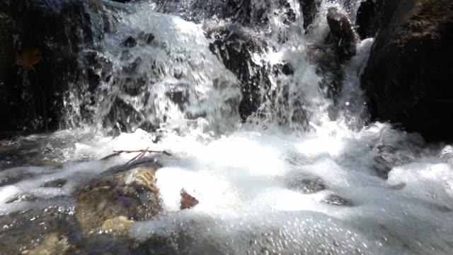 vídeos de stock e filmes b-roll de slow motion getting closer to the small waterfall. - pedra rocha