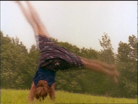vídeos de stock, filmes e b-roll de slow motion pan girl in leotard + skirt doing cartwheels in grassy field - only teenage girls