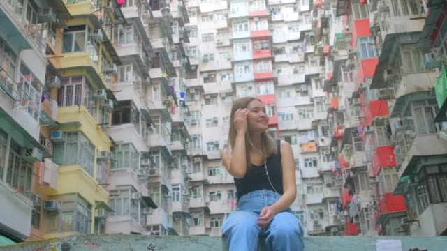 slow motion : girl listening to music located in hong kong apartment area - petite teen girl stock videos and b-roll footage