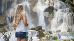 Slow Motion Girl standing and admire amazing waterfall in Luang Prabang, Laos