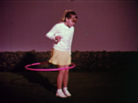 1959 slow motion girl standing on studio lawn hula hooping + lifting leg + hoop travelling around leg - 1950 1959 stock-videos und b-roll-filmmaterial