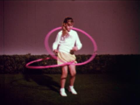 1959 slow motion girl standing on studio lawn hula hooping with 2 hoops / educational - plastic hoop stock videos & royalty-free footage