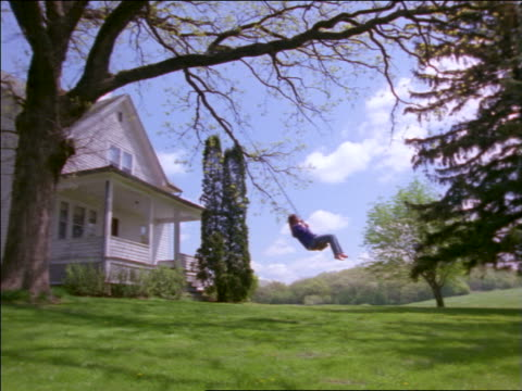 vídeos de stock, filmes e b-roll de slow motion pan girl swinging on swing from tree in front of farmhouse - only teenage girls