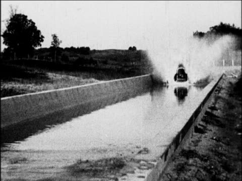 B/W 1927 slow motion GM car driving thru long canal of water / industrial