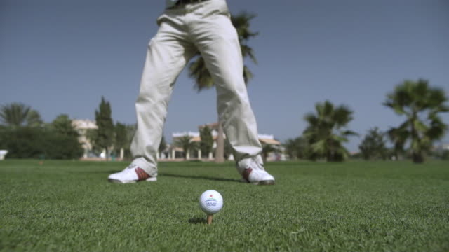vídeos de stock, filmes e b-roll de slow motion golfer driving ball from tee, spain (individual frames may also be used as a still image. each frame in its raw state is about 6mb or about 12mb as a 16 bit tiff) - tee