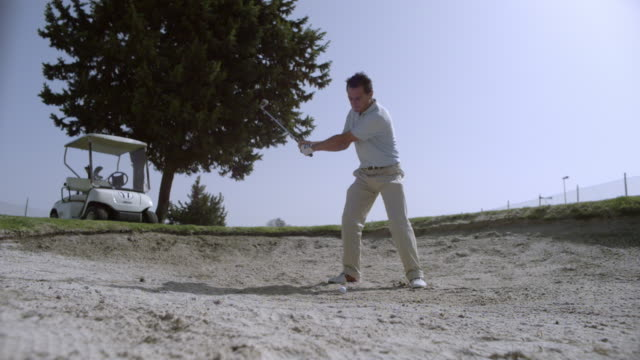 slow motion golfer hitting ball from bunker, spain (individual frames may also be used as a still image. each frame in its raw state is about 6mb or about 12mb as a 16 bit tiff) - golfball stock-videos und b-roll-filmmaterial