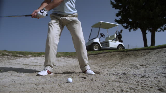 slow motion golfer hitting ball from bunker with wedge, spain (individual frames may also be used as a still image. each frame in its raw state is about 6mb or about 12mb as a 16 bit tiff) - hitting stock videos & royalty-free footage