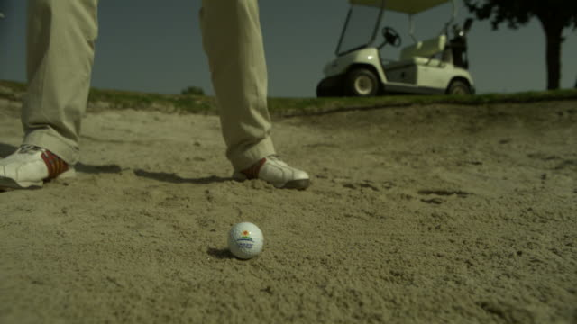 slow motion golfer hitting ball from bunker with wedge, spain (individual frames may also be used as a still image. each frame in its raw state is about 6mb or about 12mb as a 16 bit tiff) - golfer stock videos and b-roll footage