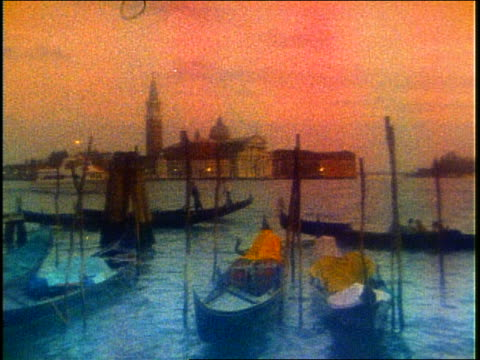 slow motion pan of gondolas on grand canal in venice / san giorgio in background / grainy - grand canal venice stock videos & royalty-free footage