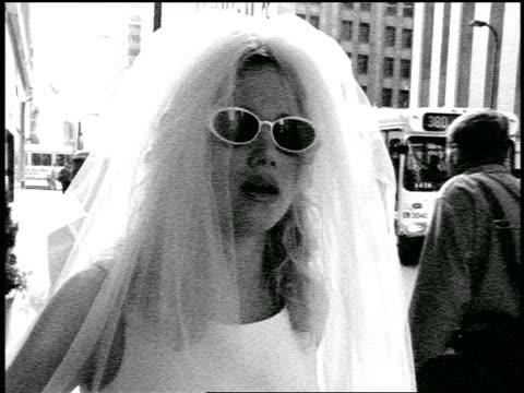 b/w slow motion grainy blonde bride in sunglasses standing on city sidewalk blowing kiss to camera - 口を尖らせる点の映像素材/bロール