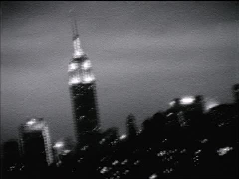 vídeos de stock, filmes e b-roll de b/w slow motion grainy pan empire state building lit up at night / new york city - centro de manhattan