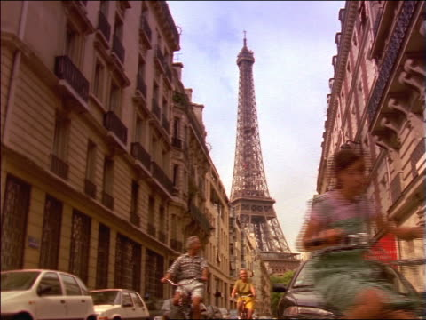 vídeos de stock, filmes e b-roll de slow motion grandparents + granddaughter riding bikes past camera away from eiffel tower / paris - french culture