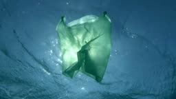 Slow Motion, Green plastic bag slowly drifting underwater surface in the sunrays. Plastic pollution of the ocean. Underwater shot, Low-angle shot, Contre-jour (backlighting).