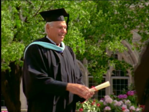 stockvideo's en b-roll-footage met slow motion grey-haired man handing diploma + shaking hands with young man at graduation ceremony - diploma