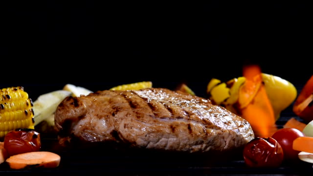 Slow motion - grilled meat /steak with vegetable on a flaming grill