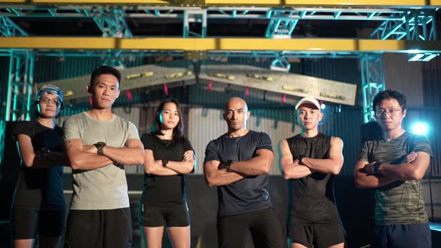 slow motion group of asian athletes arm cross in front of camera in obstacle training together. - macho stock videos & royalty-free footage