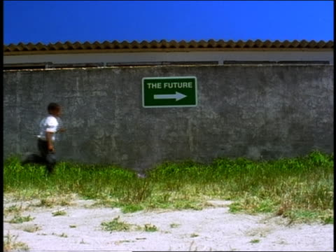 "slow motion group of black schoolchildren running past sign reading ""the future"" / south africa - barefoot stock videos & royalty-free footage"