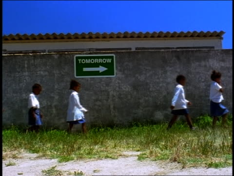 "vídeos de stock e filmes b-roll de slow motion group of black schoolchildren walking past sign reading ""tomorrow"" / south africa - perfil"