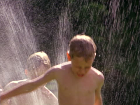slow motion group of children in swimsuits running thru sprinkler / Summer