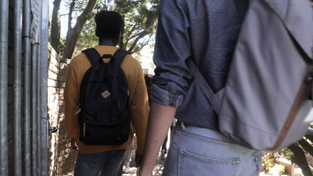 slow motion, group of college students walk on campus - rucksack stock videos & royalty-free footage