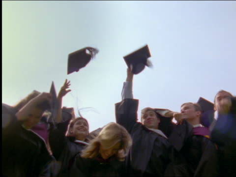 slow motion group of graduates throwing caps in air at ceremony - graduation stock videos & royalty-free footage