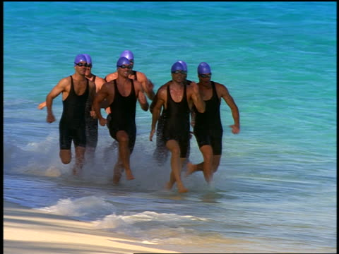 slow motion group of male triathletes in bathing caps + goggles running on beach - swimming cap stock videos and b-roll footage