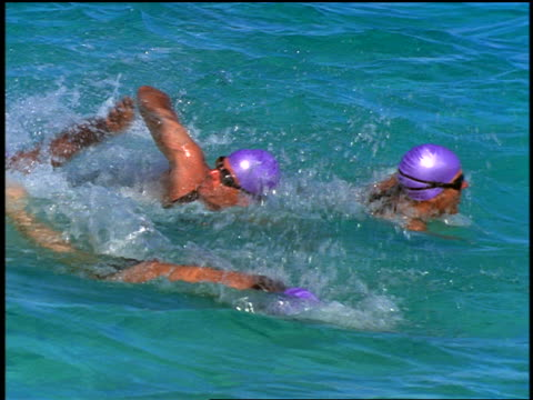 slow motion pan group of male triathletes in purple bathing caps + goggles swimming freestyle in ocean - swimming cap stock videos and b-roll footage