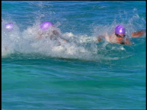 slow motion pan group of male triathletes swimming (butterfly stroke + freestyle) in ocean toward camera - swimming cap stock videos and b-roll footage