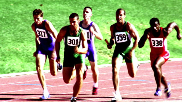 overexposed selective focus slow motion pan group of men handing off batons during relay race - lycra stock videos & royalty-free footage